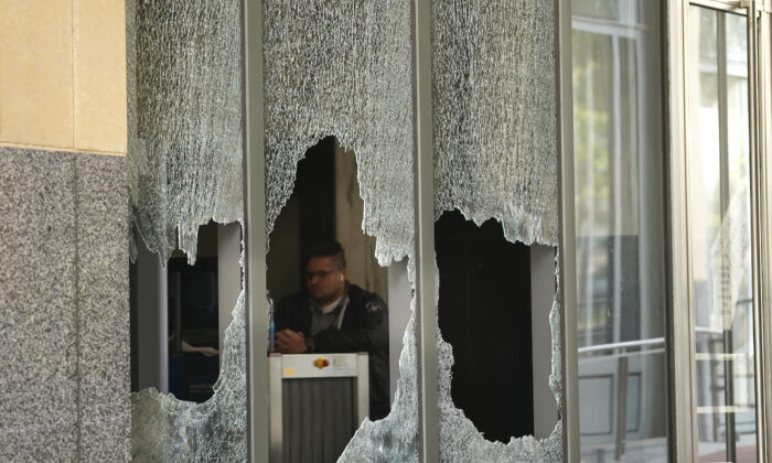 A man sits behind a broken glass from a window at the Ronald V. Dellums Federal Building in Oakland, Calif., on July 26, 2020. (Jeff Chiu/AP Photo)