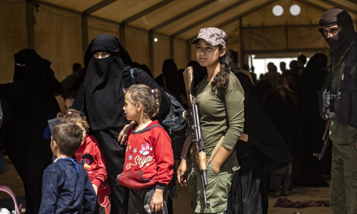 Fighters from the Syrian Democratic Forces (SDF) stand guard as displaced people prepare to board a bus waiting outside the Al-Hol camp in northeastern Syria's Al-Hasakeh governorate on June 3, 2019. (Delil Souleiman/AFP via Getty Images)