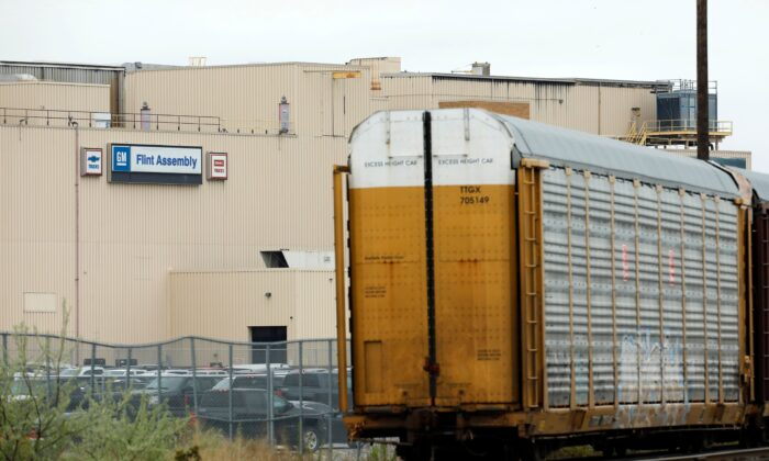 Train cars that haul vehicles are viewed outside the General Motors Flint Assembly plant in Flint, Mich., on May 18, 2020. (Jeff Kowalsky / AFP via Getty Images)