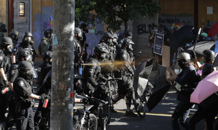 Police pepper spray demonstrators amid rioting near Seattle Central Community College in Seattle, Wash., on July 25, 2020. (Ted S. Warren/AP Photo)