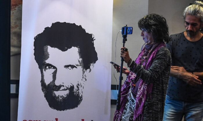 A journalist stands in front of a poster featuring jailed businessman and philanthropist Osman Kavala during a press conference of his lawyers, on Oct. 31, 2018. (Ozan Kose/AFP via Getty Images)