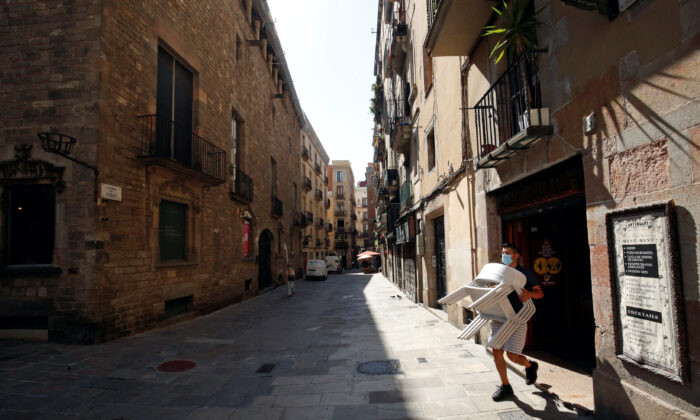 A staff member of a bar carries chairs, amid the coronavirus disease (COVID-19) outbreak, in the Gothic quarter in Barcelona, Spain, on July 27, 2020. (Albert Gea/Reuters)