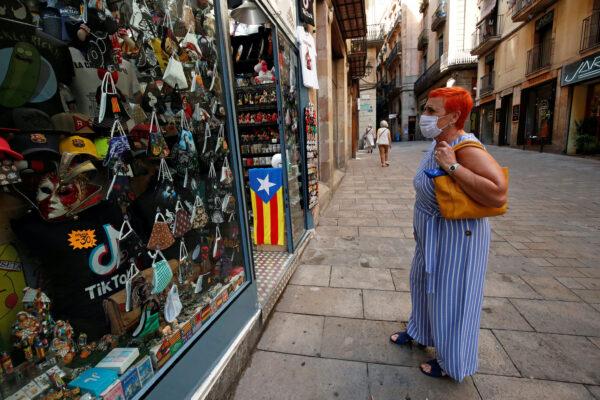 A woman looks at masks displayed at a souvenir shop Barcelona