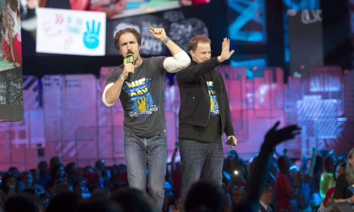 WE Charity co-founders Craig Kielburger (L) and Marc Kielburger speak during We Day in Toronto on Oct. 2, 2014. (The Canadian Press/Hannah Yoon)