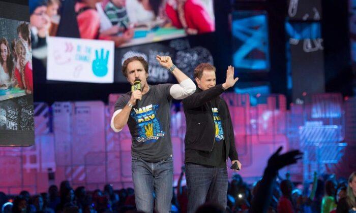 "Craig Kielburger and Marc Kielburger speak during ""We Day"" in Toronto on Oct. 2, 2014. (Hannah Yoon/The Canadian Press)"