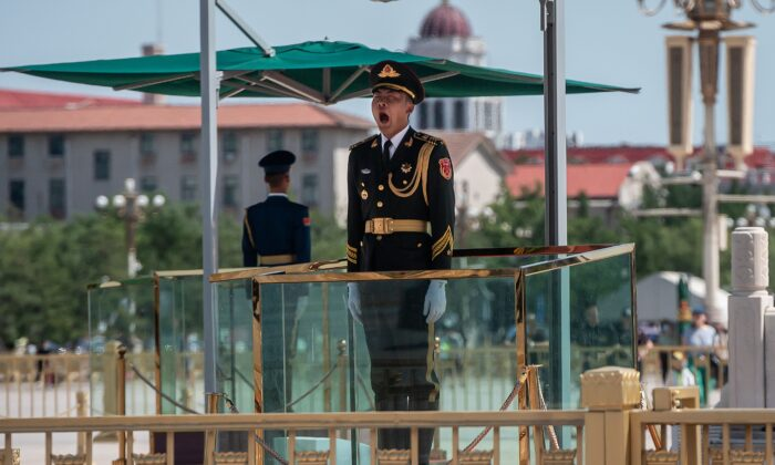 A Chinese paramilitary soldier yawns as he stands guard on Tiananmen Square in Beijing on June 4, 2020. (NICOLAS ASFOURI/AFP via Getty Images)