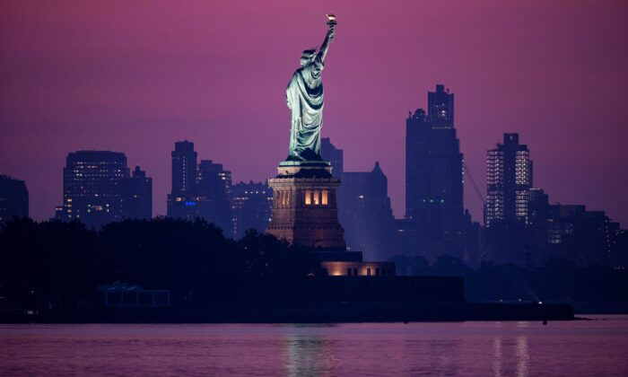 The Statue of Liberty is seen in front of the skyline of Brooklyn before sunrise in New York City on July 9, 2020. (Johannes Eisele/AFP via Getty Images)