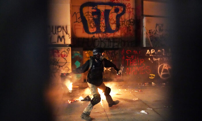 A rioter throws a flaming object toward the Mark O. Hatfield U.S. Courthouse after breaking through the perimeter fence, in Portland, Ore., on July 22, 2020.  (Nathan Howard/Getty Images)