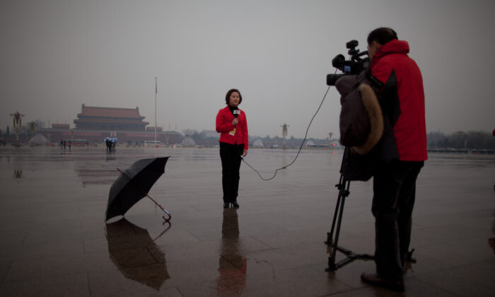 A local television reporter conducts a report from Tiananmen Square, in Beijing on March 12, 2013.  (Ed Jones/AFP via Getty Images)