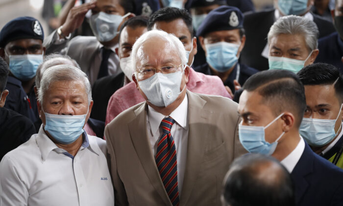 Former Malaysian Prime Minister Najib Razak, center, wearing a face mask with his supporters arrives at courthouse in Kuala Lumpur, Malaysia, on July 28, 2020. (Vincent Thian/AP)
