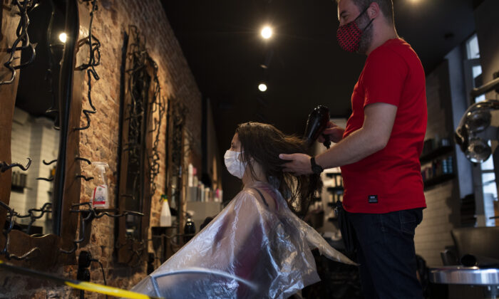 A woman, wearing a mask to protect against the spread of coronavirus, gets her hair styled in a hairdresser shop in downtown Brussels on July 27, 2020. (Francisco Seco/AP)