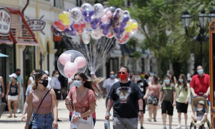 Visitors at Disney Springs walk in Lake Buena Vista, Fla., on June 16, 2020. (John Raoux/AP Photo)