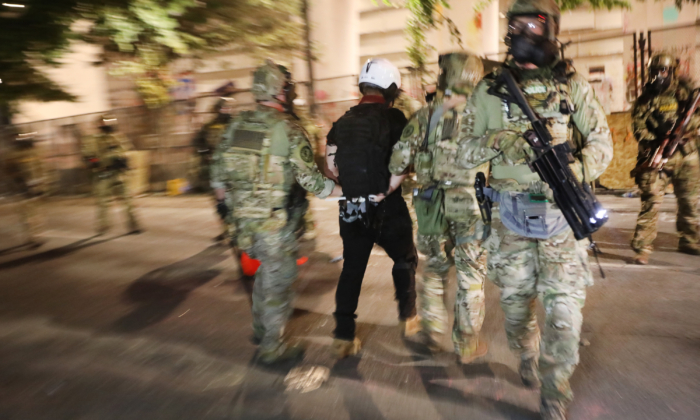 Federal police make an arrest as they confront rioters in front of the Mark O. Hatfield federal courthouse in downtown Portland on July 26, 2020. (Spencer Platt/Getty Images)