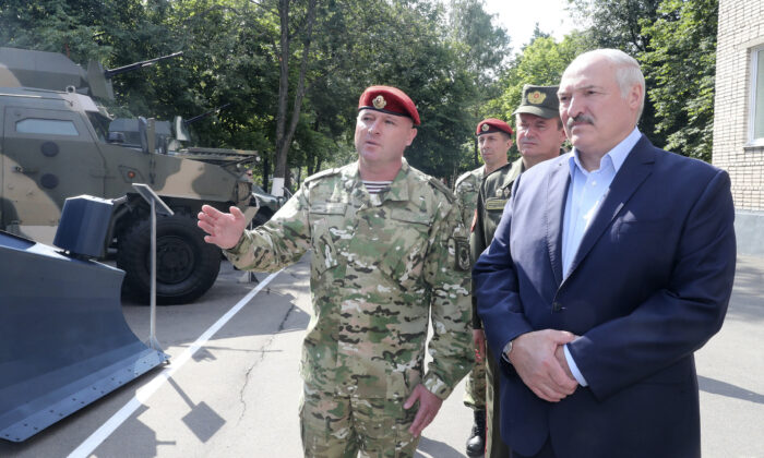 Belarus President Alexander Lukashenko, right, inspects police vehicles as he visits the Belarusian Interior Ministry special forces base in Minsk, Belarus, Tuesday, July 28, 2020. The presidential election in Belarus is scheduled for Aug. 9, 2020. (Nikolai Petrov/AP Photo)
