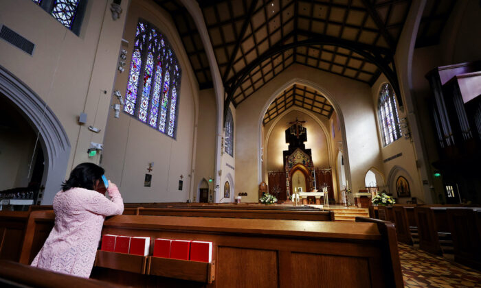 APRIL 12:  A woman prays at the St. Agnes Cathedral on Easter Sunday on April 12, 2020 in Rockville Center, New York.   (Al Bello/Getty Images)