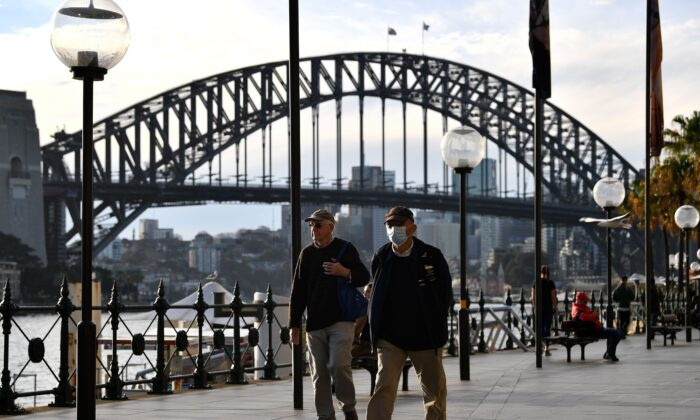 A man wearing a face mask walks before the Harbour Bridge in Sydney, NSW, Australia on July 22, 2020. (Saeed Khan/AFP via Getty Images)