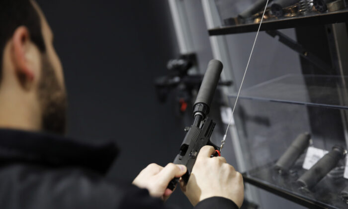 A visitors pulls the slide of a pistol with a silencer at a gun displays at a National Rifle Association outdoor sports trade show in Harrisburg, Penn.,  on Feb. 10, 2017. (Dominick Reuter/AFP via Getty Images)