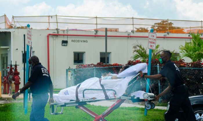 Emergency medical technicians leave with a patient at North Shore Medical Center, where COVID-19 patients are treated, in Miami, Fla., on July 14, 2020. (Maria Alejandra Cardona/Reuters)