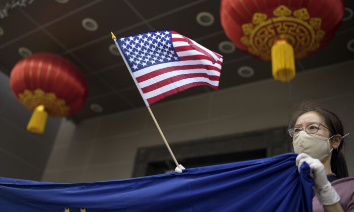 A protester holds a U.S. flag outside of the Chinese consulate in Houston on July 24, 2020, after the U.S. Department of State ordered China to close the consulate. (MARK FELIX/AFP /AFP via Getty Images)