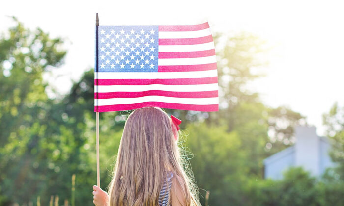 File photo of a young girl with an American flag. (JillWellington/Pixabay.com)