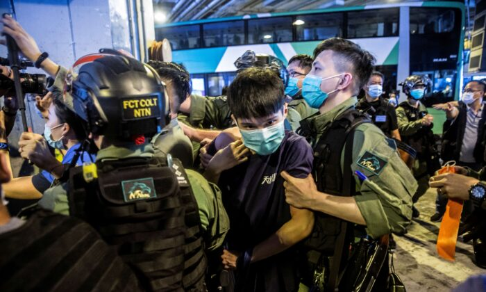 A riot police officer (R) detains a man (C) during a protest by district councillors at a mall in Yuen Long in Hong Kong on July 19, 2020, against a mob attack by suspected triad gang members inside the Yuen Long train station on July 21, 2019. (Isaac Lawrence/AFP via Getty Images)