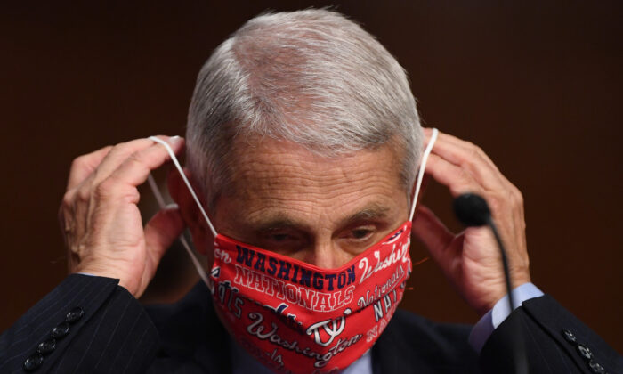 Anthony Fauci, director of the National Institute for Allergy and Infectious Diseases, lowers his face mask before testifying at a Senate committee in Washington on June 30, 2020. (Kevin Dietsch-Pool/Getty Images)
