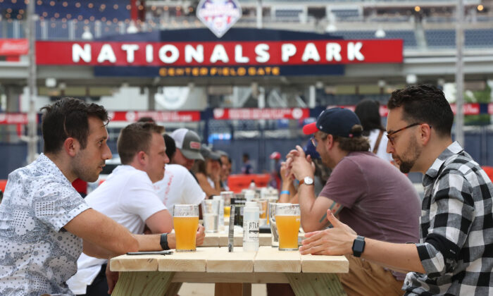 Baseball fans drink beer while gathering outside Nationals Park during the Opening Day game between the Washington Nationals and the New York Yankees in District of Columbia on July 23, 2020. (Win McNamee/Getty Images)