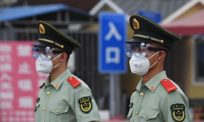Paramilitary police officers wear face masks and goggles as they stand guard at an entrance to the closed Xinfadi market in Beijing on June 13, 2020. (GREG BAKER/AFP via Getty Images)