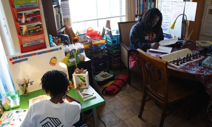 Ayinde (L), age 10, and Zion, 17, do their school work at their home in Washington, on Feb. 24, 2017. (MANDEL NGAN/AFP via Getty Images)