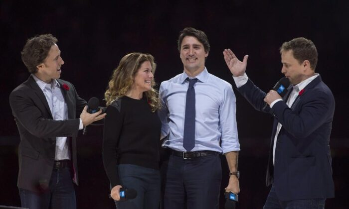 Co-founders Craig (L) and Marc Kielburger introduce Prime Minister Justin Trudeau and his wife Sophie Gregoire-Trudeau as they appear at the WE Day celebrations in Ottawa on November 10, 2015. (The Canadian Press/Adrian Wyld)