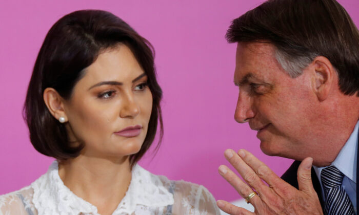 Brazil's President Jair Bolsonaro talks with his wife Michelle Bolsonaro during a ceremony marking International Women's Day at Planalto Palace in Brasilia, Brazil, on March 6, 2020. (Adriano Machado/Reuters)