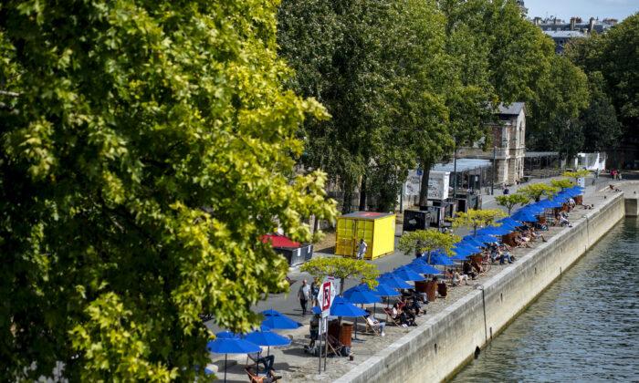 People sit along the river Seine in Paris July 28, 2020. (Kamil Zihnioglu/AP Photo)