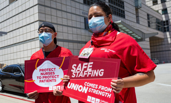 Nurses David Yamada, left, and Emily Carrera hold signs at a protest over working conditions due to the COVID-19 pandemic outside the Ronald Reagan UCLA Medical Center in Los Angeles, Calif., on July 29, 2020. (John Fredricks/The Epoch Times)