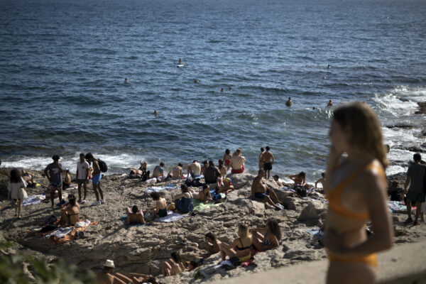People enjoy the sun at the Malmousque Beach in Marseille, in southern France