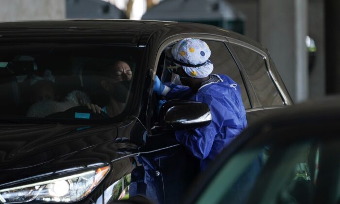 A medical worker takes a swab from a driver at a drive-thru COVID-19 testing site at the Mahaffey Theater in St. Petersburg, Fla., on July 24, 2020. (Bryan R. Smith/AFP via Getty Images)