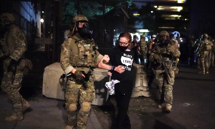 "Federal officers arrest a woman wearing a ""Black Lives Matter"" shirt outside the Mark O. Hatfield Courthouse in Portland, Ore., in the early hours of July 30, 2020. (Nathan Howard/Getty Images)"
