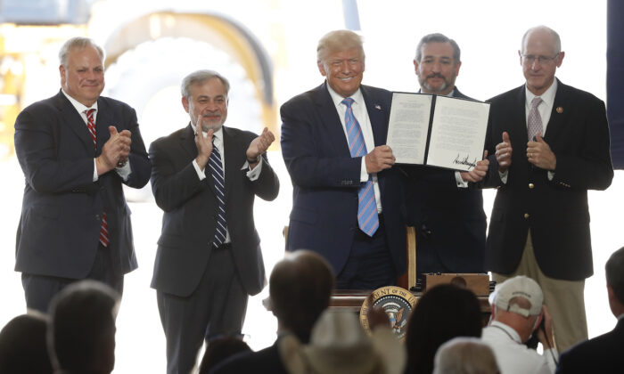 President Donald Trump holds up a permit for energy development after signing it during a visit to the Double Eagle Development oil rig, in Midland, Texas, on July 29, 2020. (Tony Gutierrez/AP Photo)