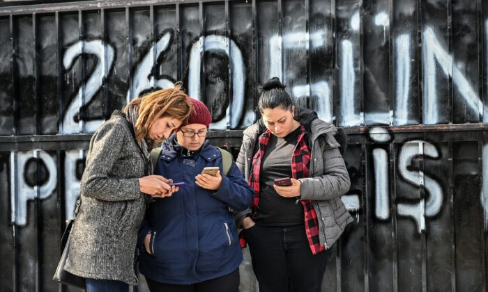Some of the 132 women laid off from the Flormar Cosmetics Company's Kocaeli factory, which the French cosmetics group Yves Rocher holds a 51-percent stake, check their mobile phones as they continue their daily protest outside the factory grounds after being dismissed on May 15, 2019, in Gebze on Jan. 29, 2019. (Ozan Kose/AFP via Getty Images)