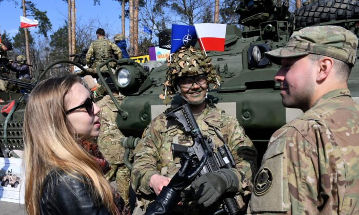 U.S. soldiers speak with a woman in the Wesola district of Polands capital Warsaw on March 29, 2017. (Janek Skarzynski/AFP via Getty Images)