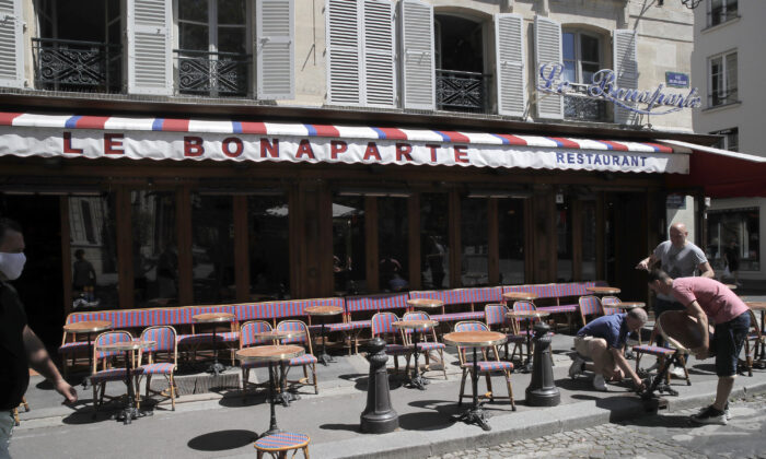 Waiters prepare the terrace of a restaurant in order to respect distancing measures in Paris as France gradually lifts its lockdown due to the coronavirus, on June 1, 2020. (Christophe Ena/AP Photo)