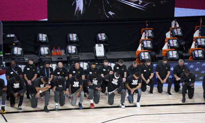 Players and other personnel kneel during the national anthem before the start of an NBA basketball game between the New Orleans Pelicans and the Utah Jazz in Lake Buena Vista, Fla., on  July 30, 2020. (Ashley Landis/Pool/AP Photo)