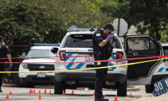 Chicago Police investigate at the 25th District station on the northwest side, in Chicago, after several officers were shot outside the station, Chicago, on July 30, 2020. (Ashlee Rezin Garcia/Chicago Sun-Times via AP)