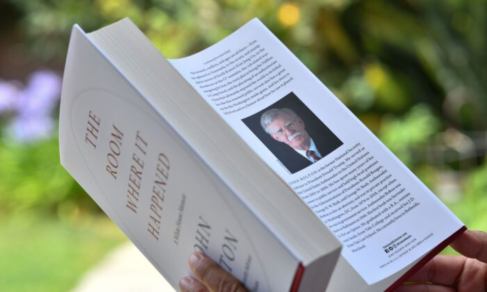 "A reader holds John Bolton's book ""The Room Where It Happened,"" in Glendale, Cali., on June 23, 2020. (Chris Delmas/AFP/Getty Images)"