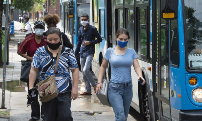 Passengers wearing masks to protect against COVID-19 disembark from a bus in Montreal on July 27, 2020. Federal political parties are seeing a significant drop in donations this year as the pandemic continues to impact the lives and pocket books of Canadians. (The Canadian Press/Ryan Remiorz)