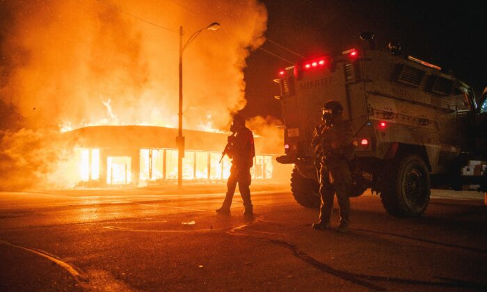 A police armored vehicle patrols an intersection while a building set afire by rioters burns in Kenosha, Wis., on Aug. 24, 2020. (Brandon Bell/Getty Images)