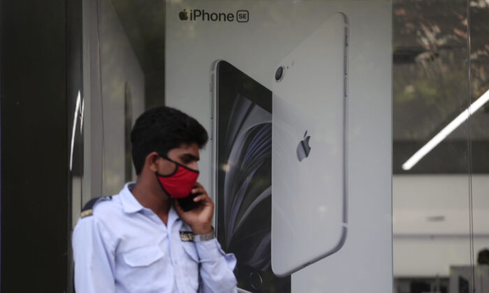 A security officer talks on a phone in front of an image of an iPhone displayed at an Apple store in Ahmedabad, India, Saturday, Aug. 1, 2020. (Ajit Solanki/AP Photo)
