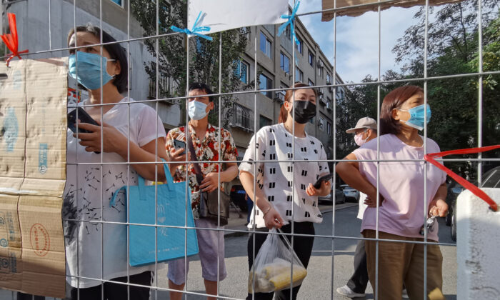 Residents wait for groceries delivered to an entrance of a sealed residential compound, after new cases of COVID-19 were confirmed in Dalian city, Liaoning Province, China, on July 23, 2020. (China Daily via REUTERS)