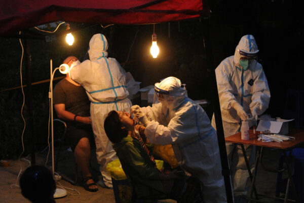 Workers collect swabs for nucleic acid testing at a makeshift testing site in Dalian