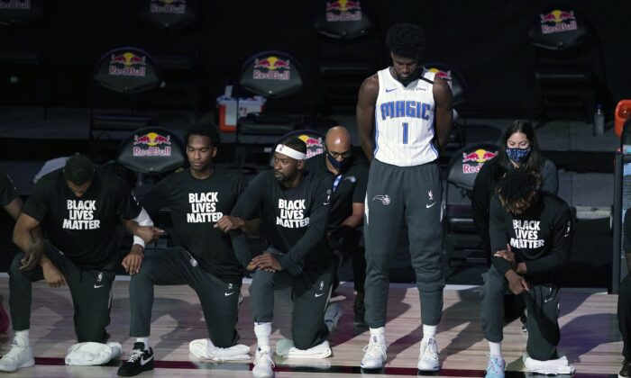 Orlando Magic's Jonathan Isaac (1) stands as others kneel before the start of an NBA basketball game between the Brooklyn Nets and the Orlando Magic in Lake Buena Vista, Fla., on July 31, 2020. (Ashley Landis/Pool/AP Photo)