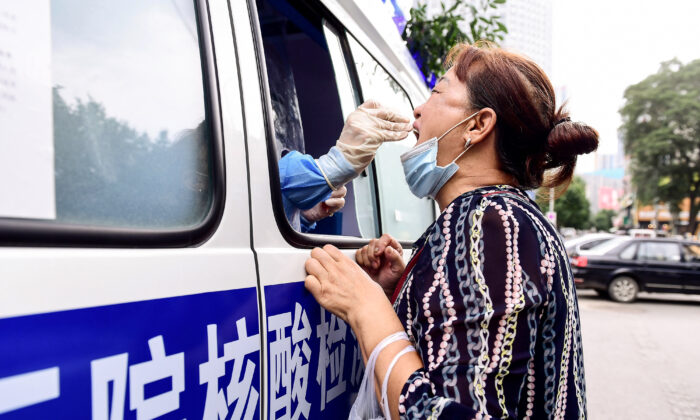 A health worker carries out a COVID-19 test on a resident in a testing vehicle in Shenyang in China's northeastern Liaoning Province on July 29, 2020. (STR/AFP via Getty Images)